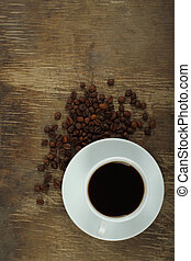 Coffee cup with beans on an old wooden background close-up