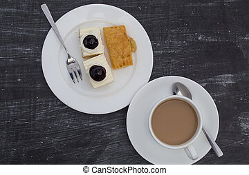 Coffee cup with blueberry cheesecake on white dish