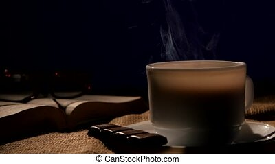 Coffee cup with book, glasses and bar of chocolate, on black background