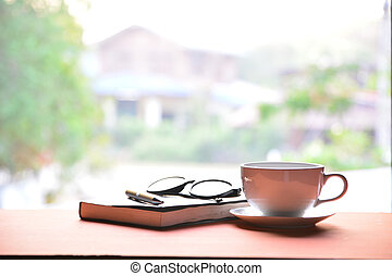 Coffee cup with book, pen and glasses on a wooden table