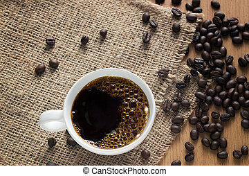 Coffee cup with bubbles and beans on a sack background, top view, soft focus