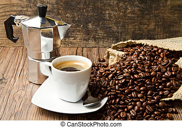 Coffee cup with burlap sack of roasted beans on rustic table...