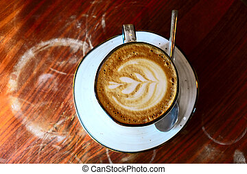 Coffee cup with cappuccino on the worn polished tabletop top view