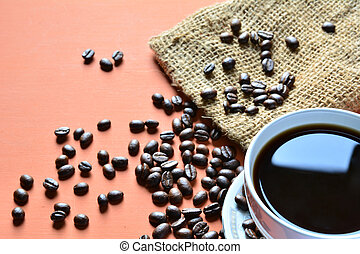 Coffee cup with coffee beans and sack on a orange background