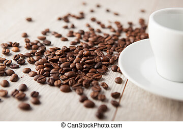 coffee cup with coffee beans scattered