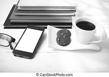 coffee cup with cookie, phone, stack of book and eyeglasses black and white color
