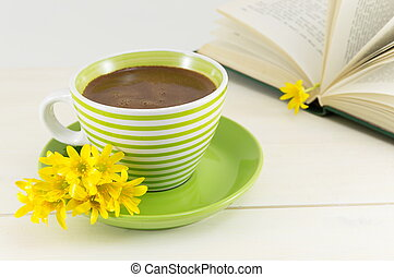 coffee cup with fresh flowers and a book