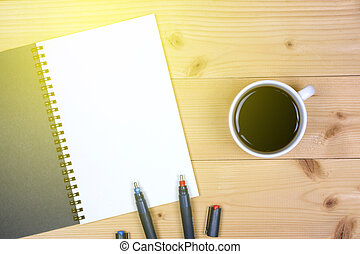 Coffee cup with note book on table