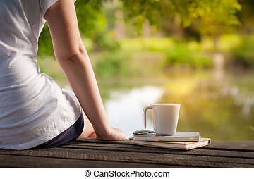 Coffee cup with notebook on rustic wood table - Young woman...