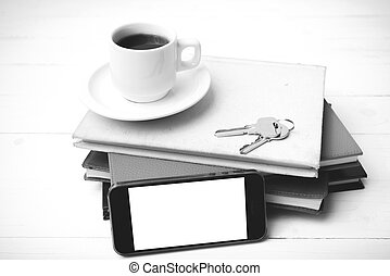 coffee cup with phone, key and stack of book black and white color