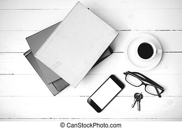 coffee cup with phone, key, eyeglasses and stack of book black and white color