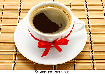 Coffee cup with red bow on a wooden background