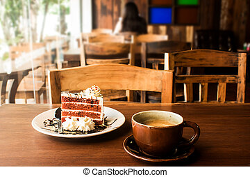 Coffee cup with slice of cake on wood table in cafe