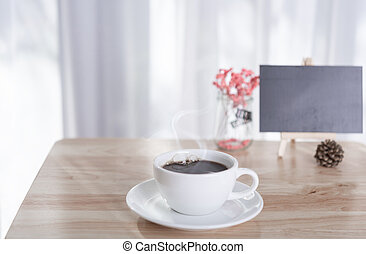 coffee cup with smoke and black board on office table with white curtain background in morning light