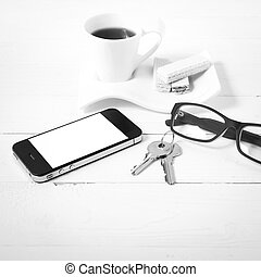 coffee cup with wafer, phone, key, eyeglasses black and white color