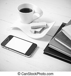 coffee cup with wafer, phone, stack of book black and white color