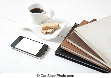 coffee cup with wafer, phone, stack of book
