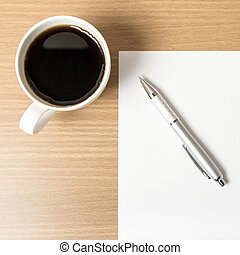 coffee cup with white paper and pen