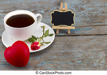 coffee cup,heart and red rose with blackboard with empty space for a text over wooden background