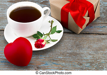 coffee cup,heart and red rose with gift box over wooden...