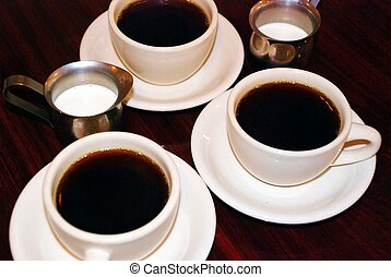 Three hot cups of coffee and two silver creamers on a brown table.