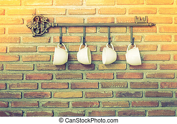 Coffee cups hanging on hooks in front of brick wall ( Filtered i