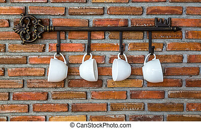 Coffee cups hanging on hooks in front of brick wall