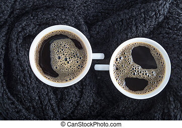 Coffee cups wrapped a black woolen scarf