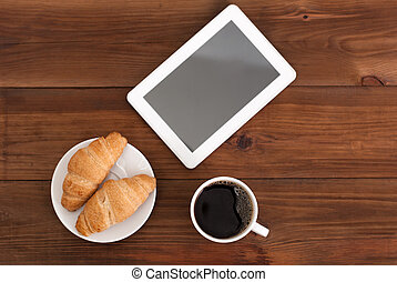 Coffee digital tablet and croissants on a wooden table.