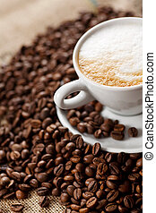 Coffee foam - A pile of coffee beans with cup of coffee in...