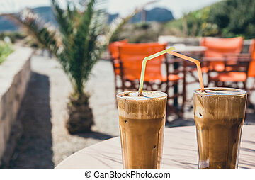 Coffee frappe, greek cuisine on the table at the beach,...