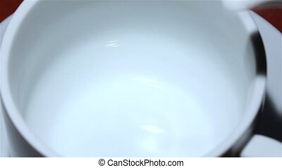 Coffee from the pot is poured into a white cup