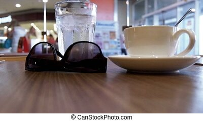 Coffee, glass of cold water and sun glasses on the table and defocused shopping mall and crowd of walking people on background with bokeh