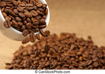 Coffee grains fall from a cup