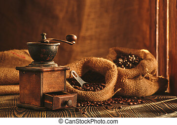 Coffee grinder and bag of roasted coffee on wooden table.