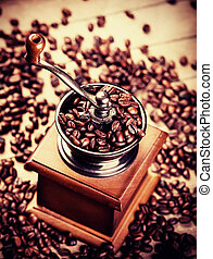 Coffee grinder with coffee grains on a wooden table