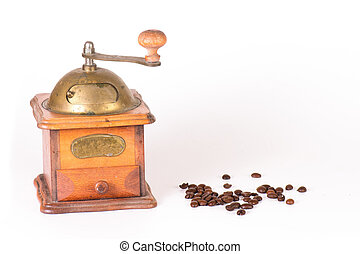 Coffee grinder with some grains scattered on a white