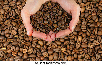 Coffee hands - Two woman hands holding coffee beans over a...