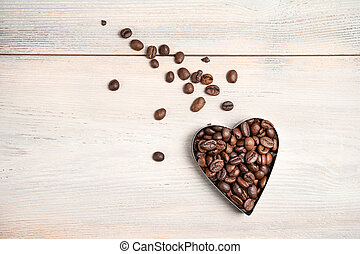 Coffee heart on a light background. A flying heart with a tail of scattered grains.