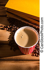 Coffee in a disposable Cup with roasted coffee beans, a stack of books on the table, close-up, space for text
