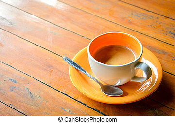 coffee in ceramic orange cup on wooden table