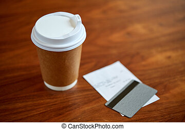 coffee in paper cup, bill and credit card on table - payment...