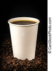 Coffee in paper cup on natural coffee beans on dark
