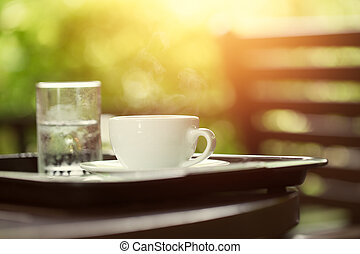 coffee in the morning with water glass, cup of espresso on wood table in cafe or coffeeshop.