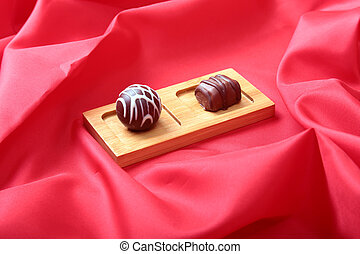 Coffee in white cup with chocolate pralines on red background