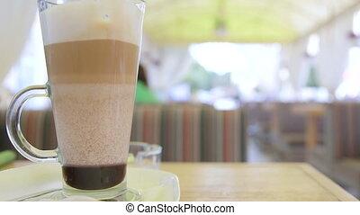Coffee latte cup on table of sidewalk cafe rack focus