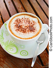 Coffee latte or cappuccino in a cup on wooden background