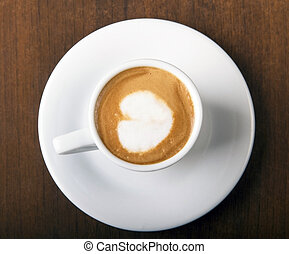 Coffee Macchiato directly above, served in white cup, on wooden table