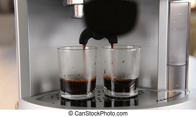 coffee machine in operation fills two glass cup of coffee....