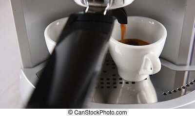 coffee machine in operation fills two white cup of coffee....